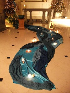 Turquoise fabric is laid out as a river pouring from the altar during a Meditative Eucharist