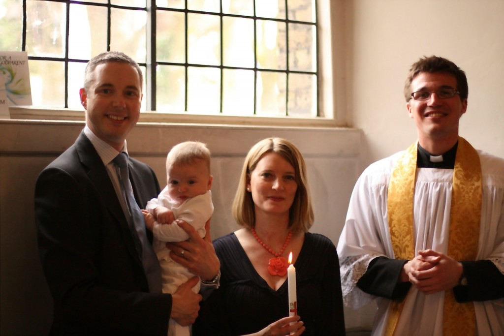 A newly baptised baby with their parents and former curate, Fr Owen Dobson