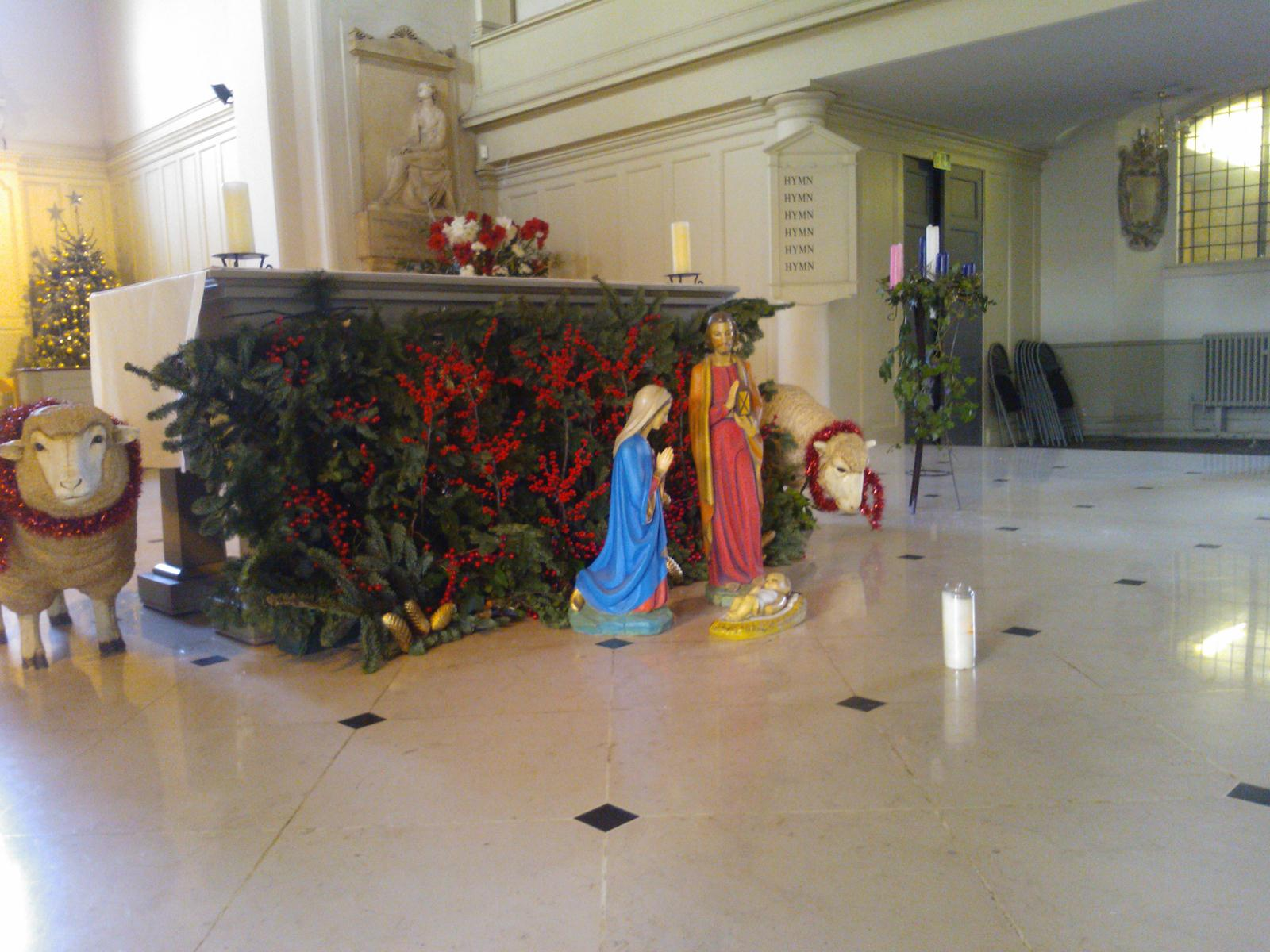 The altar at St John's Wood Church at Christmas, decked in green and red with a nativity scene in front of it