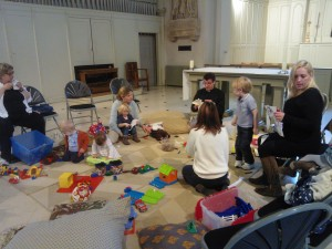 Toddlers play in the chancel, under the direction of Fr Owen and the watchful eye of their carers (who have fun too!)