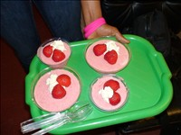 Four pink mousses on a tray, each topped with strawberries and cream