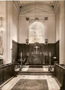The chancel and altar, with wood panelling on the walls and carpet leading up to the altar